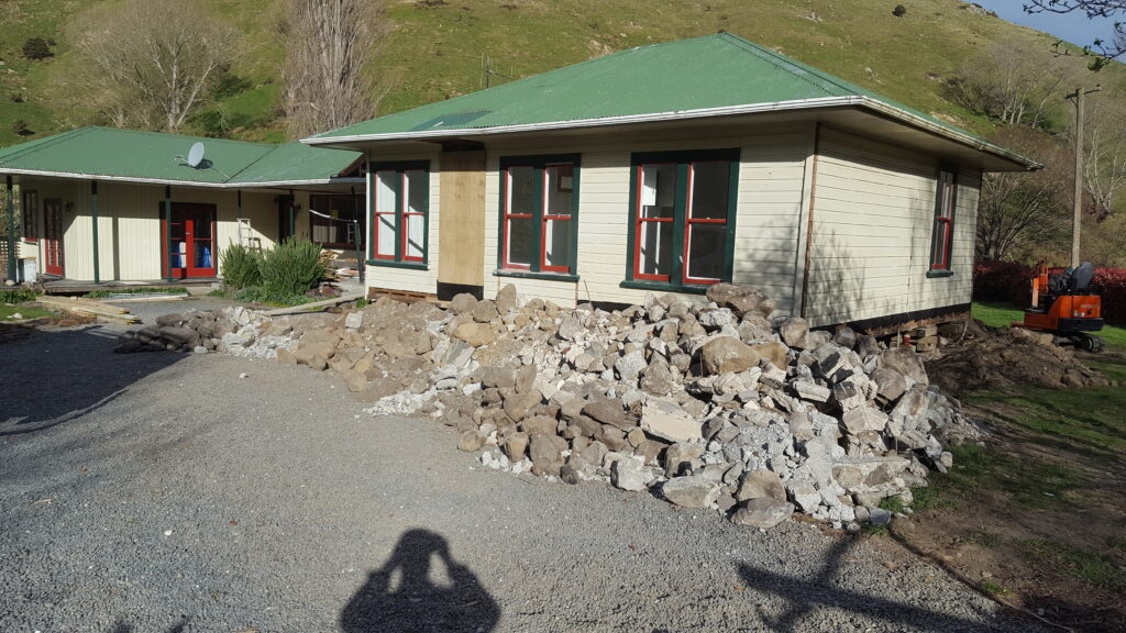 green and white house with rubble in Kaikoura