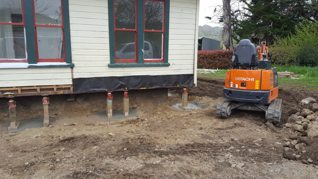 digger creating a moat around earthquake damaged house