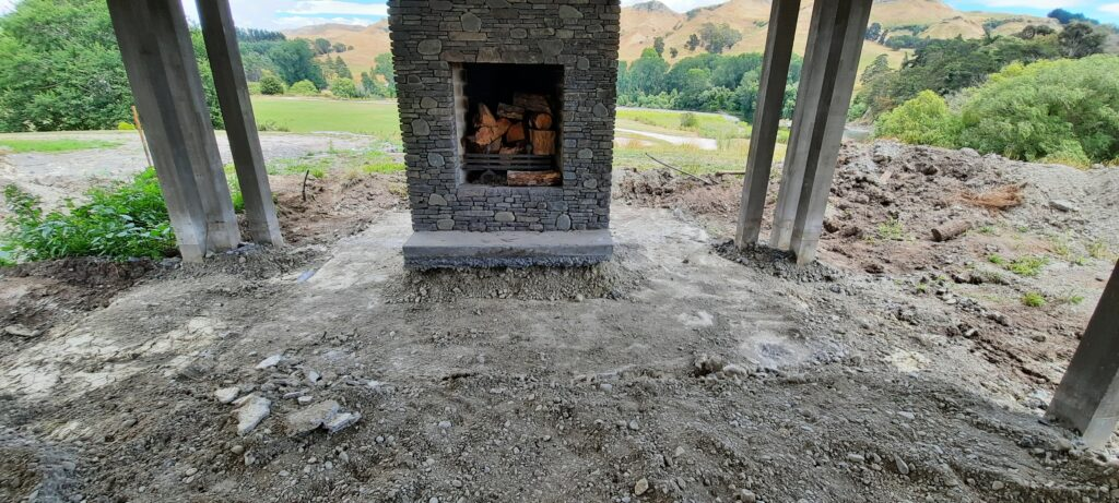 Outdoor undercover fireplace sits upon newly relevelled foundations with hills in background